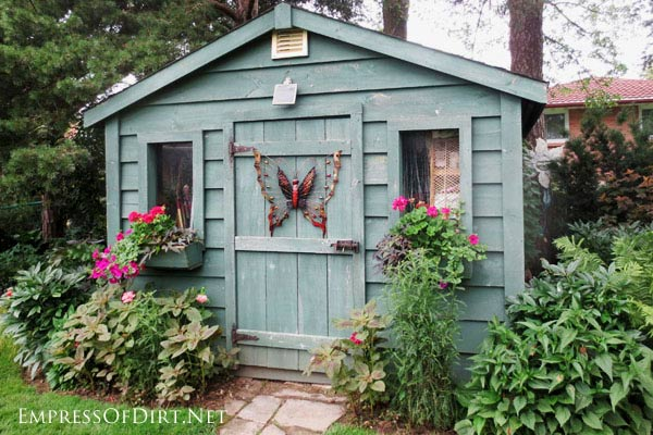 Blue garden shed with butterfly metal art on door.
