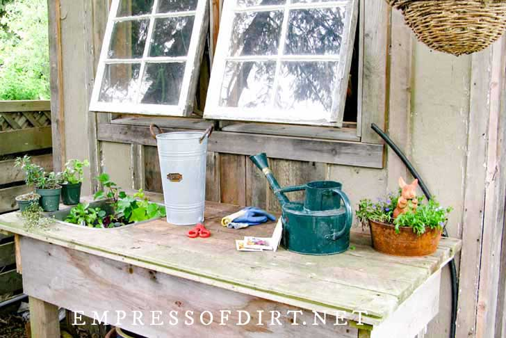 Rustic potting bench with green watering can.