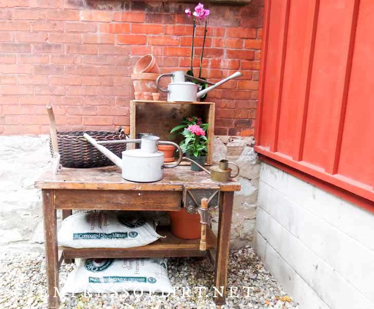Wooden table used as a potting bench with watering cans and bags of potting mix.