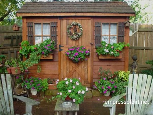 Wood stained garden shed with pink flowers on door.