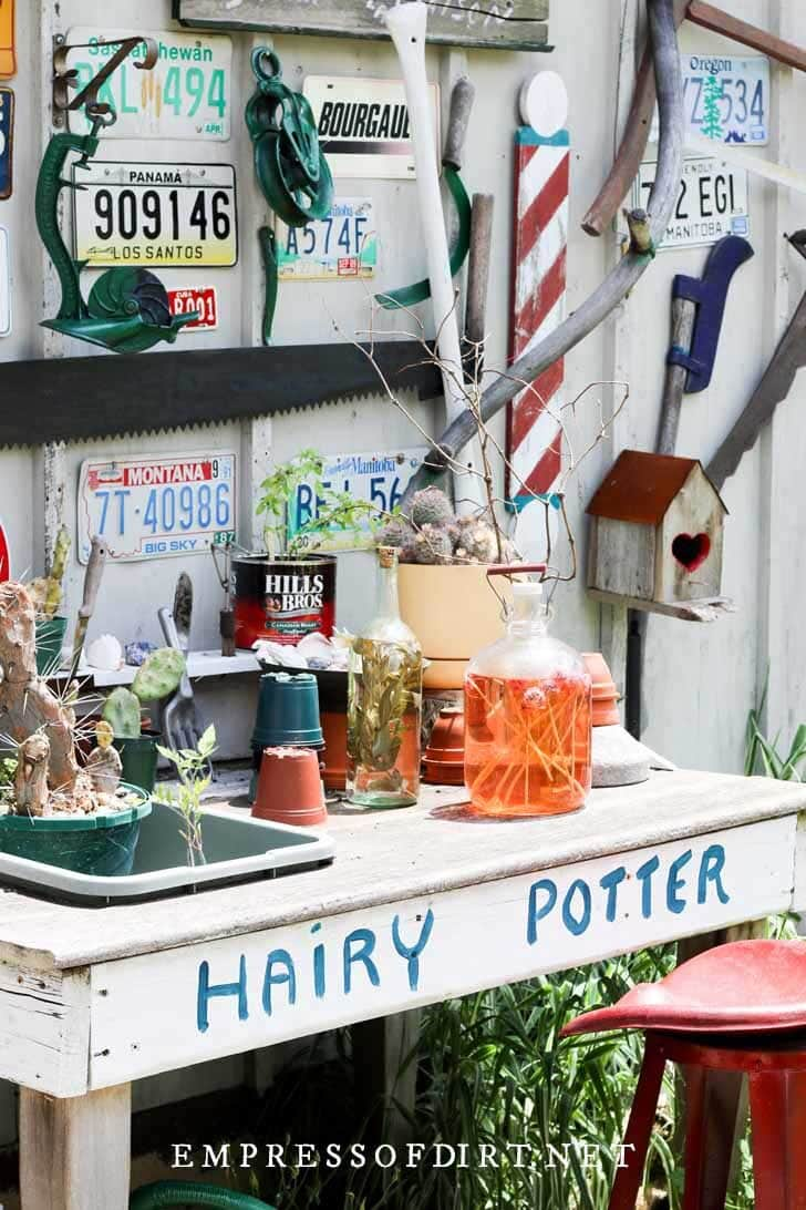 Hairy Potter potting bench with jars of potions and garden supplies.