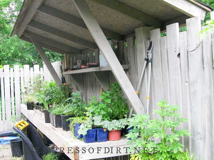 Potting bench with potted plants with rooftop overhead for rain protection.
