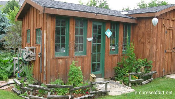 Wood garden shed with green window trim.