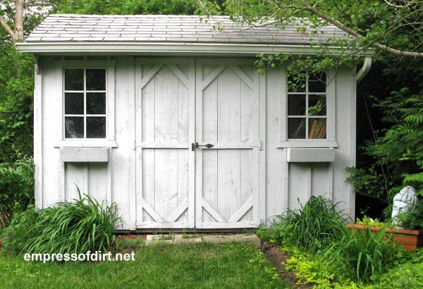 White washed garden shed with double barn doors.