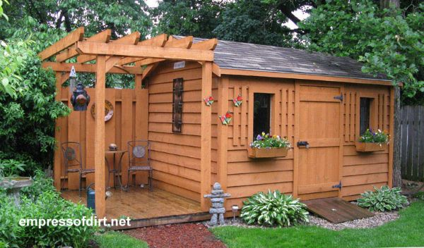 Wood stained garden shed with side seating area and arbor.