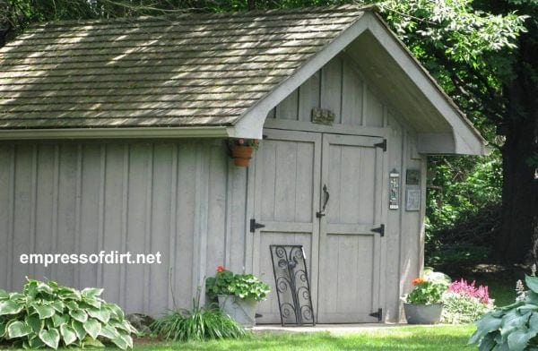 Board and batten taupe shed with wide doors.
