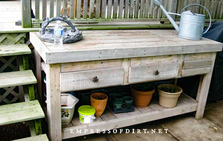 Solid, plain wood potting table with flower pots stored on lower shelf.