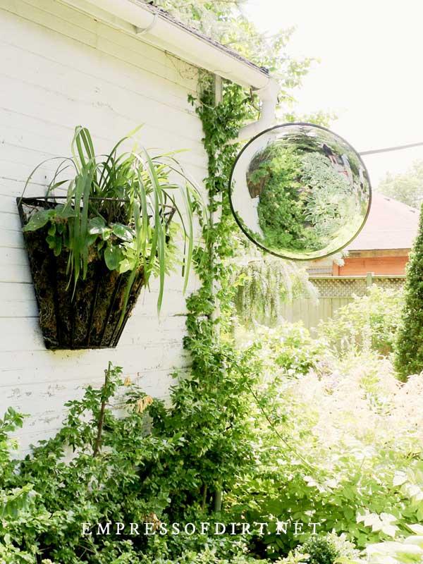 Convex mirror in green garden.