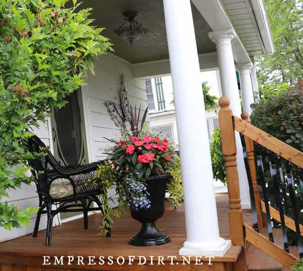 Victorian front porch with pillars, wicker chair, and black urn filled with flowers.