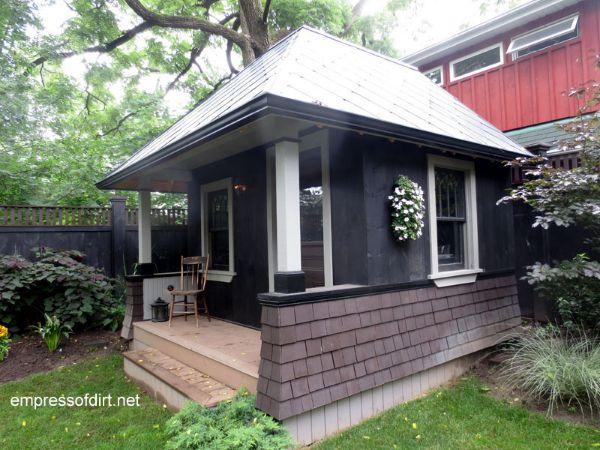 Small black garden shed with porch and steps.