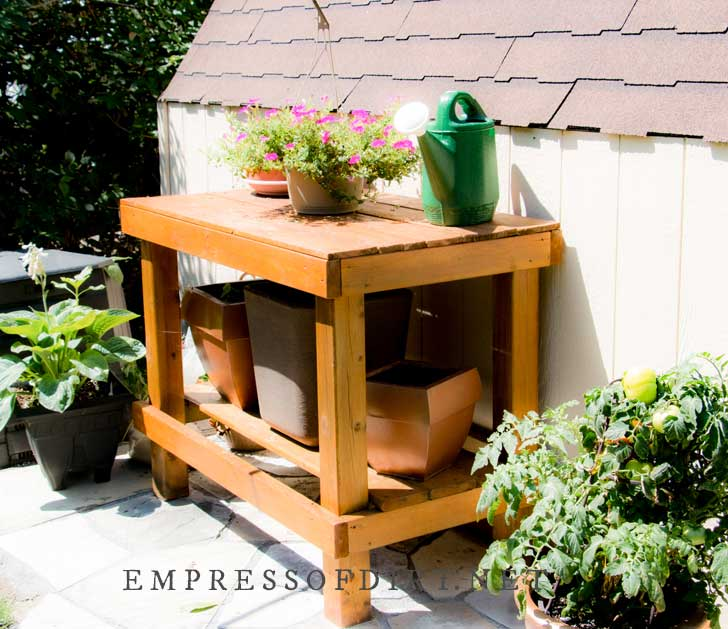 Tall, wood-stained potting table in garden with flower pots and watering can.