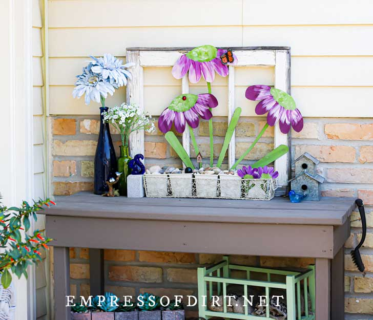 Gray table-style potting bench with decorative, metal garden art flowers.