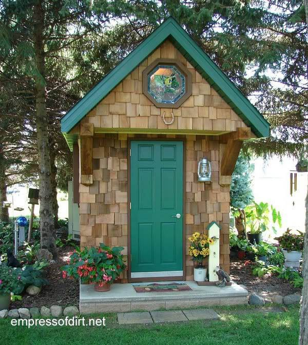 Narrow garden shed with stained glass window above door.