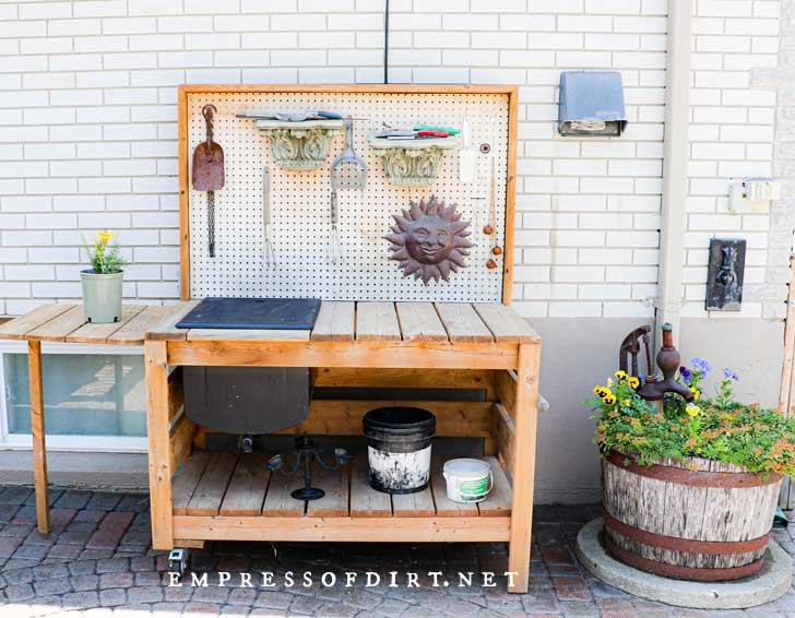 Wood potting bench with back tool holder and lower shelves.