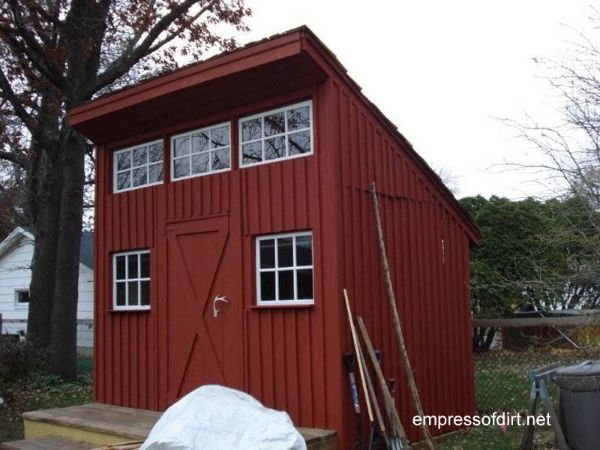 Tall narrow deep red shed with three windows over door.