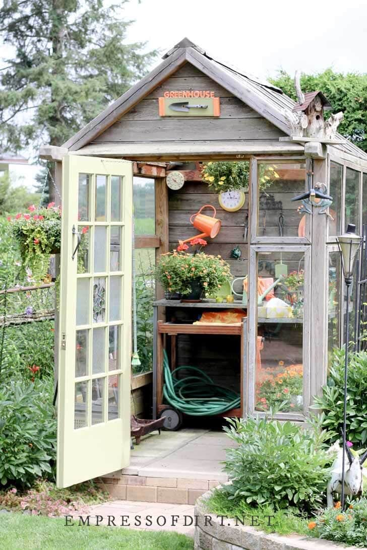 Decorative potting shed with built-in potting tables inside.