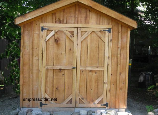 Plain wood shed with double doors.