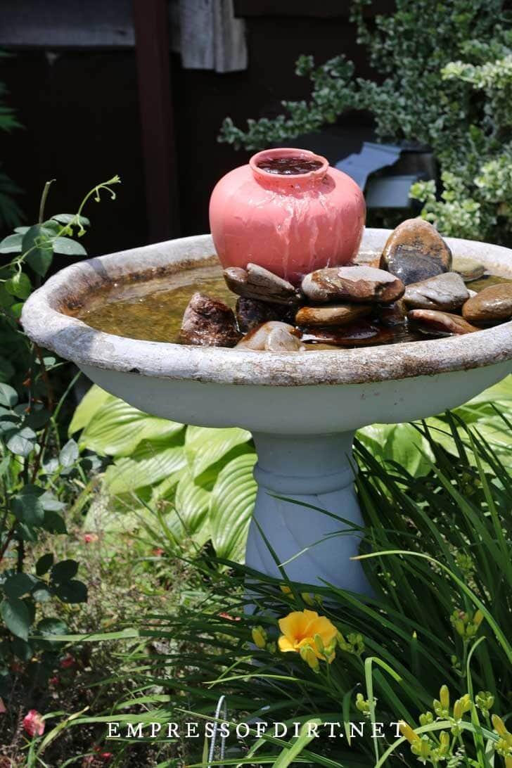 Birdbath with jug water fountain.