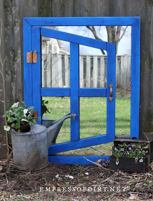 Optical illusion garden mirror with blue painted frame.