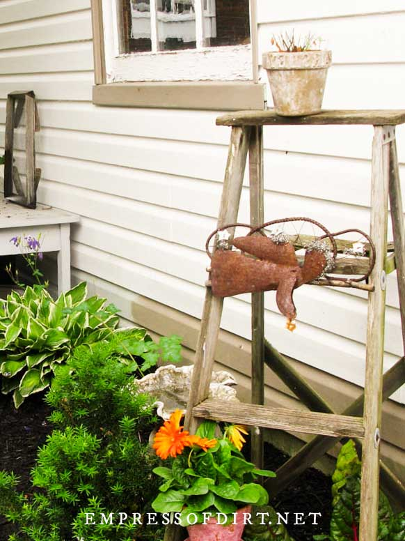 Garden art ladder with angel decor.