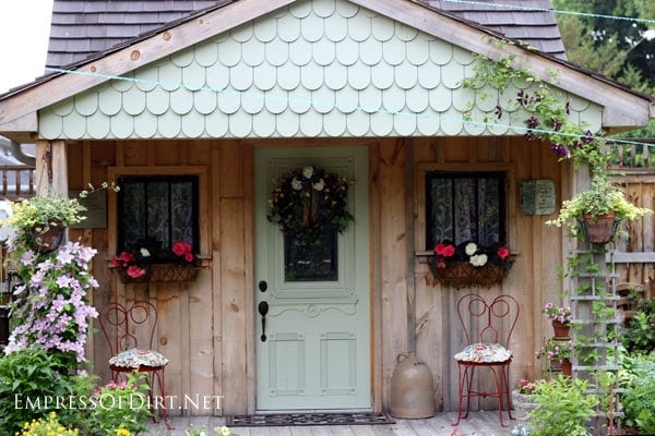 Charming garden shed with window baskets and scalloped roof.