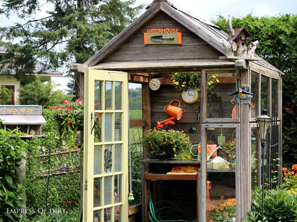 Glass and wood greenhouse used as a potting shed.