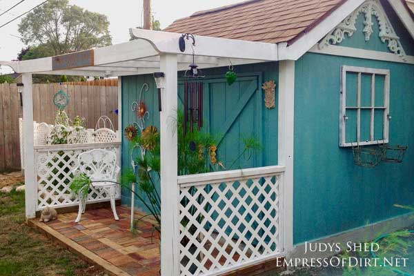 Turquoise blue garden shed with white trim and decor.
