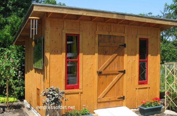 Wood stained garden shed with red framed windows.