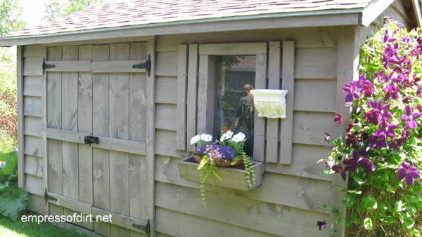 Taupe garden shed with wide double doors and simple shutters.