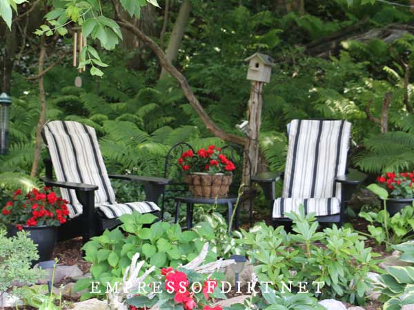 Seating area in garden with two Adirondack chairs with striped cushions, a birdhouse, and bright red flowers in planters.