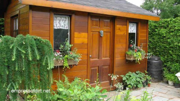 Wood stained shed with window boxes and lion's head door knocker.
