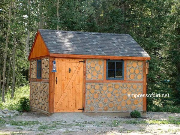 Wood cord shed with wide door at side.