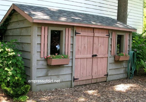 Wood shed with gray walls and pink doors and shutters.