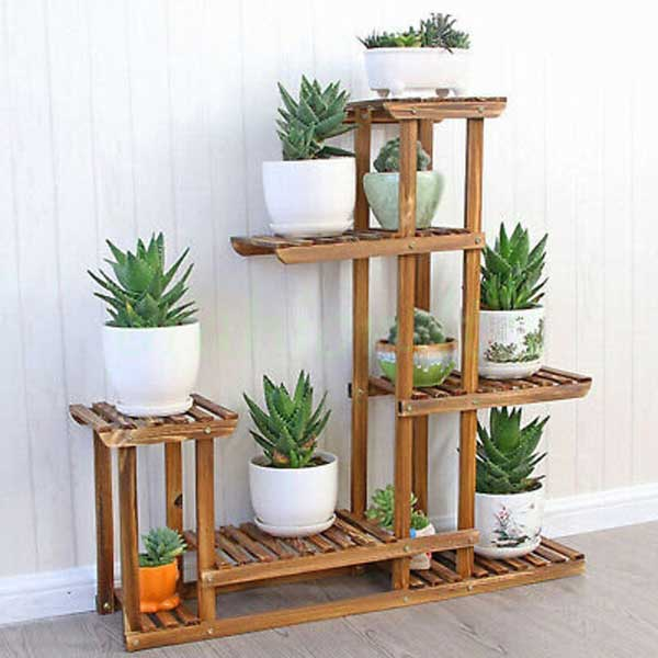 Multi-layer wooden plant shelf with potted plants.