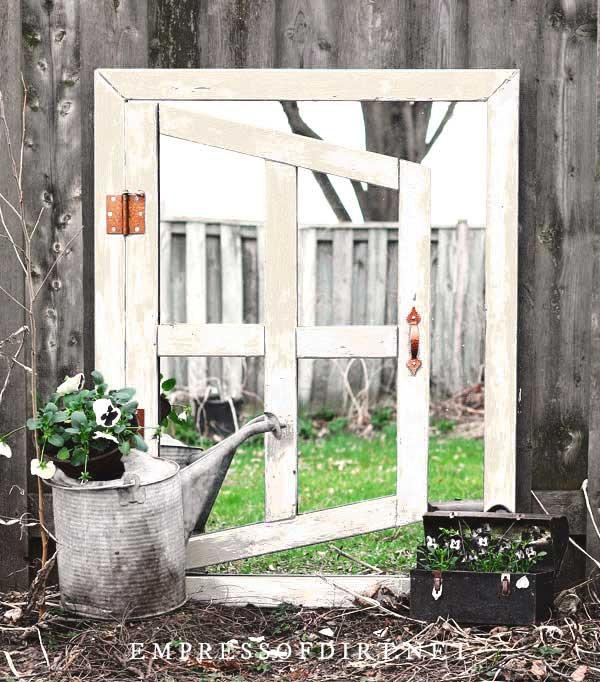 White painted optical illusion garden mirror.
