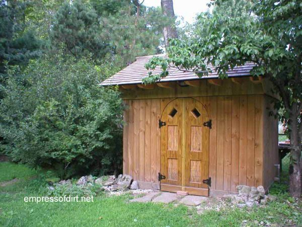 Wood shed with vertical wall boards and curved door.
