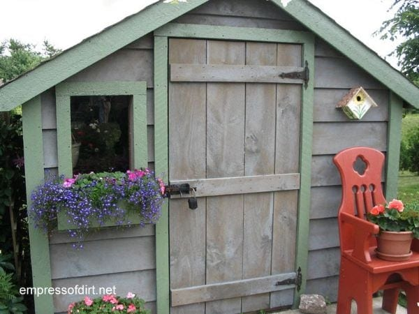 Weathered wood shed with light green stained trim.