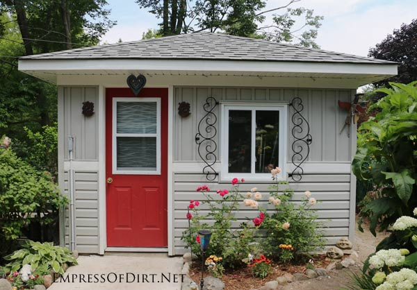 Light taupe shed with red door and metal garden art.