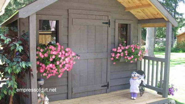 Taupe garden shed with baskets of pink flowers.