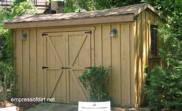 Light mustard color garden shed with wide doors and side wall windows.