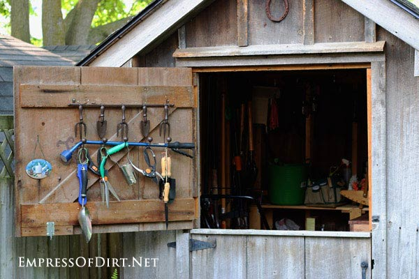 Garden shed with dutch door with garden tools.