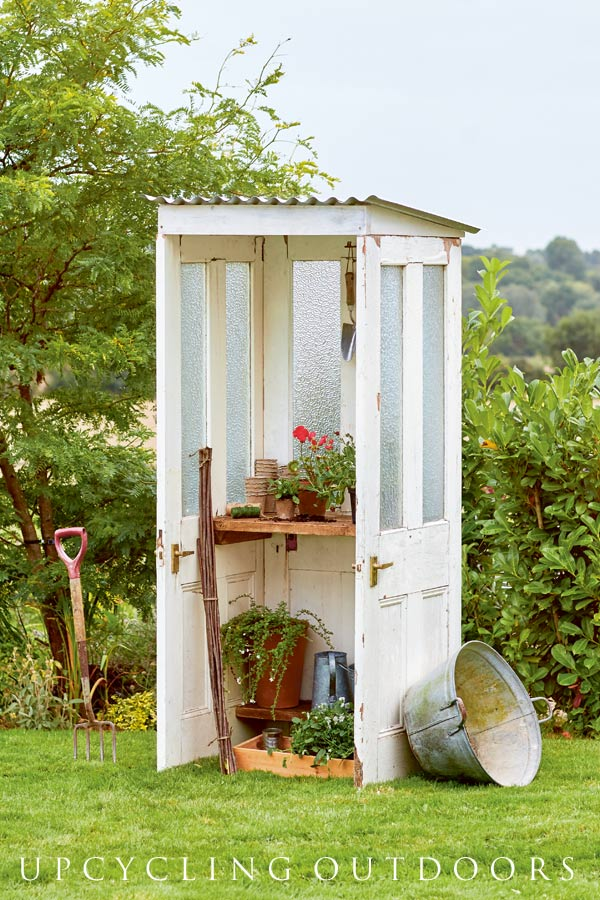 Tall, narrow potting shed made from reclaimed old doors.