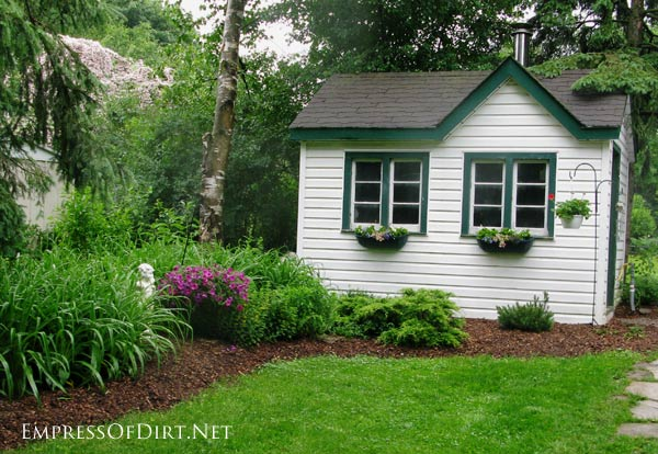 White garden shed with green trim windows and roof line.