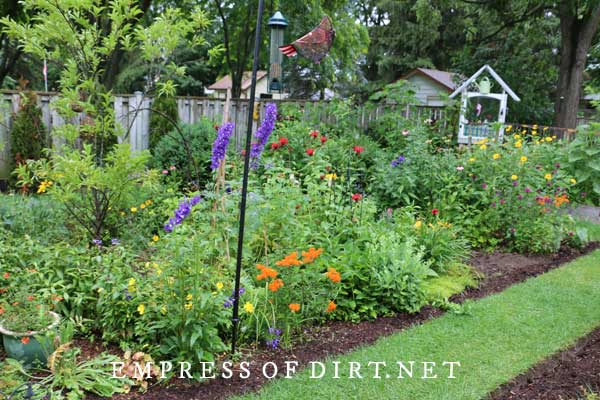 Perennial flower garden with purple, orange, and red blooms.