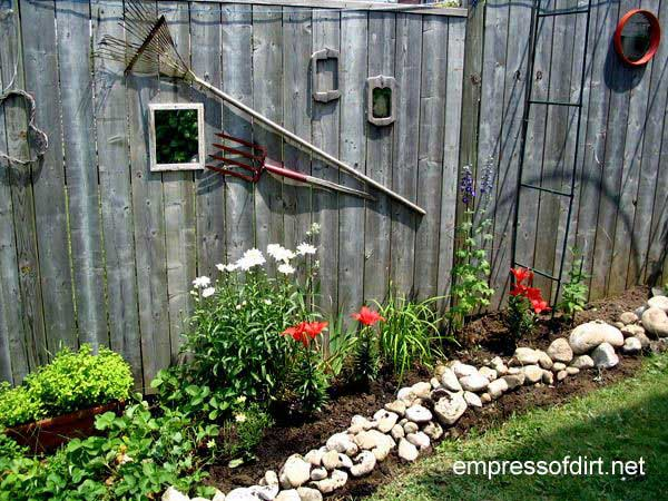 Small framed mirror and old tools on garden fence.