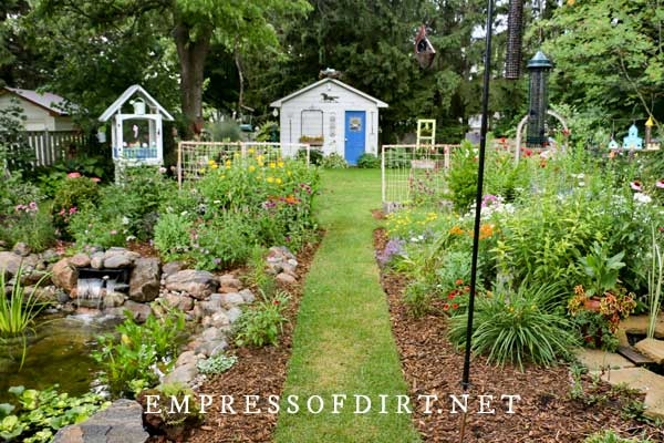 Backyard garden with ponds, flowers, and shed.