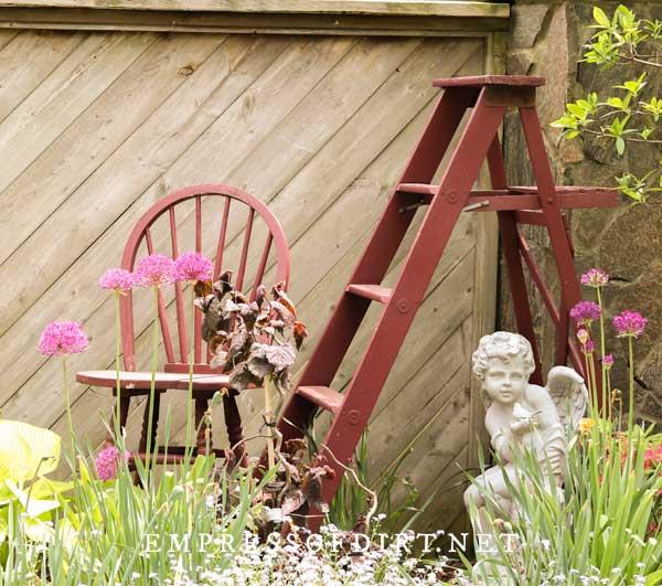 Red garden art ladder, chair, and angel in garden.