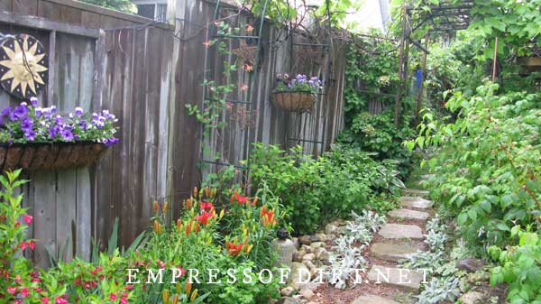 Garden path and fence with garden art.