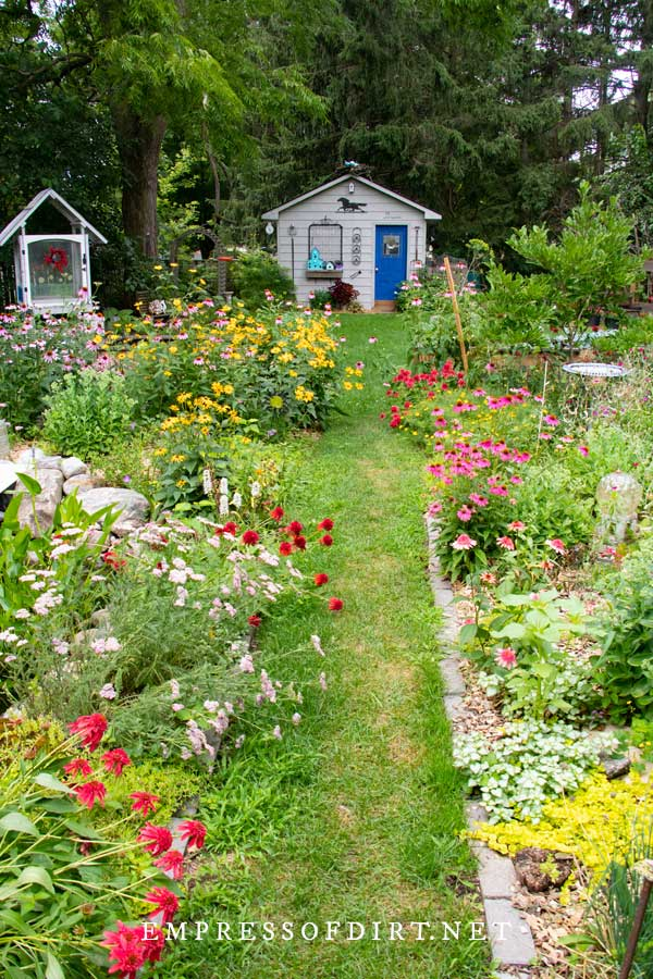 Backyard garden with colorful flowers and shed.