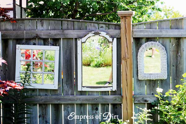 Three white framed mirrors on garden fence.